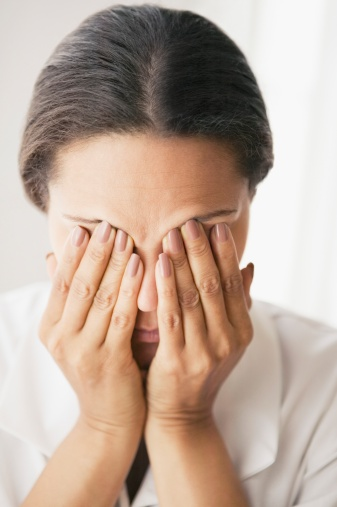 Hispanic woman rubbing eyes